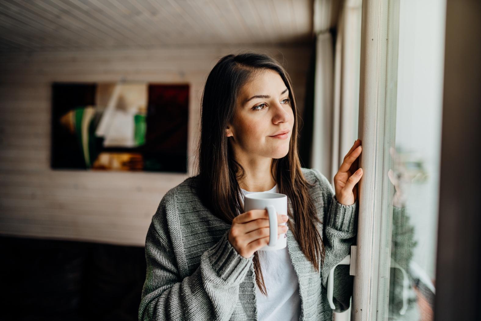 Mujer mira por la ventana durante el distanciamiento social